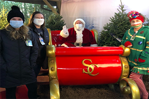 Image of 2 people wearing masks standing next to Santa and elf in masks