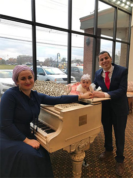 Image of woman wearing a hijab and dress sitting at a piano holding hands with a man standing next to the piano with a baby laying on the piano in between them