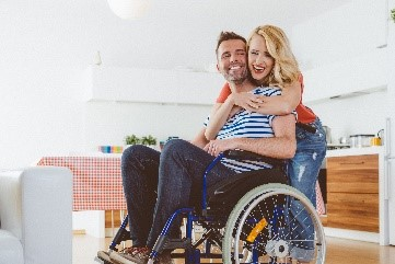 Image of man in a wheelchair and woman smiling and hugging