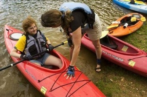 Joanne Garlow of the Special Olympics kayaking team helps Ashley Thompson with her kayak last month