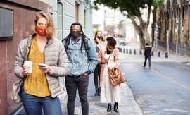 women with short red hair wearing a mask and a man behind her in a blue shirt wearing a mask walking down the street