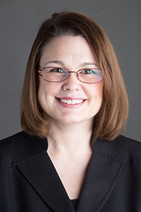 Headshot of Sara Gelser, caucasian brunette woman in a suit and wearing glasses.