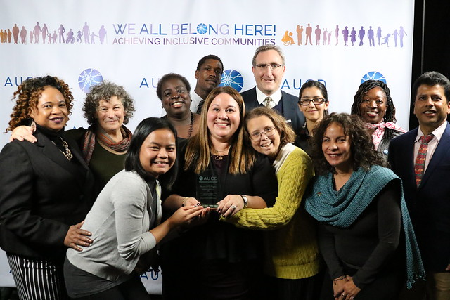 Men and women of different ages and races and abilities, all dressed up, huddle together and smile at the camera. The woman in the center is holding a glass award engraved with AUCD.