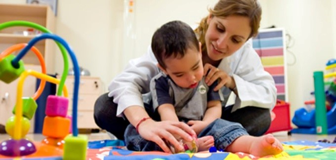Image of a child and physical therapist