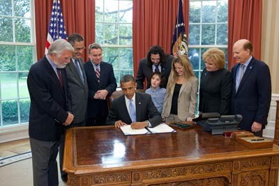 George Jesien (AUCD); Scott Badesch (ASA); Rep. Chris Smith (R-NJ); Jasper, Billy (Autism Speaks), and Gena Mann; and Suzanne and Bob Wright (Autism Speaks) with President Obama as the Combating Autism Reauthorization Act is signed.