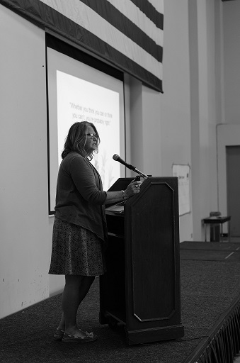 Photo of Cate Weir speaking at the podium during the event.