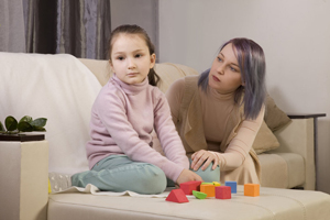 Photo of mother and child sittiong on a couch with building blocks