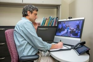 From his desk at Vanderbilt, Jeff Hine, Ph.D., uses telemedicine to perform an evaluation for autism with a patient in another city via videoconference, reducing travel burdens for the family. Photo by John Russell.