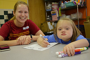 A child works on an art project at Camp Munroe while recreational therapy staff member Anna Reelfs looks on.