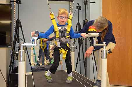 Caption: Wyatt Fisher gets ready to rock the treadmill as Munroe-Meyer Institute physical therapist Marne Iwand checks the position of his feet.