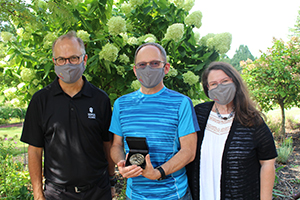 Stephan Viehweg wearing a mask holding an award alongside two colleagues who are also wearing masks.
