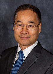 Image of an Asian man with short hair and glasses wearing a suit and ties smiling at the camera.