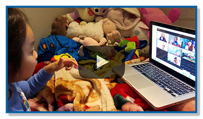 Image of a child sitting with their blanket and stuffed animals participating virually in class with a laptop in front of them.