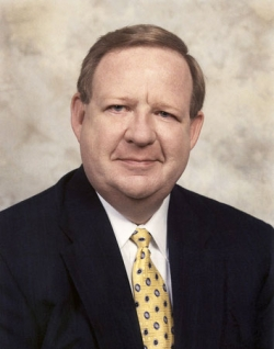 Image of a older white man wearing a suit and tie smiling at the camera.