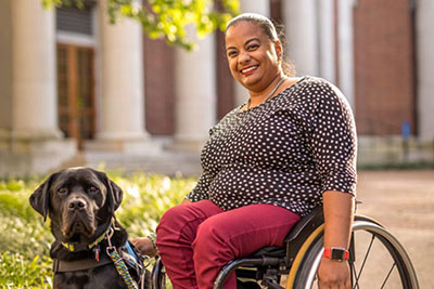 Image of a black woman with her hair pulled back using a wheelchair with a servic og sitting besides her.