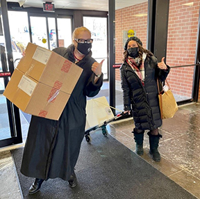 Image of two masked women walking through office doors carrying boxes.