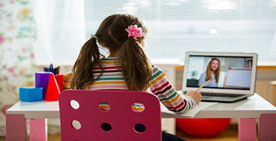 Image of a young girl wearing pigtails sitting at a desk with a opened laptop in front of her with her back to the camera.