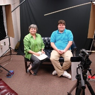 Image of a woman and a man sitting in front of a video camera in front of a backdrop