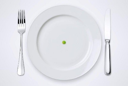 Image of a white plate with a green pea in the center with a fork and knife on each side.