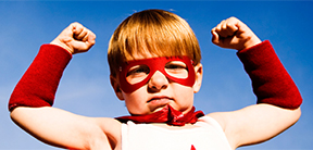 Image of a boy wearing a red cape flexing his muscles