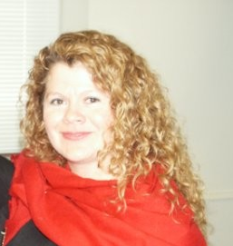 Headshot of Silvia Gutiérrez Raghunath. She has long curly blonde hair. She wears a black top with a red scarf on top.