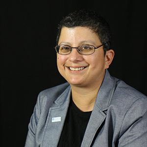 Image of a woman with short cropped hair and glasses wearing a suit and smiling at the camera.