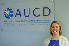 A young woman stands next to the AUCD sign