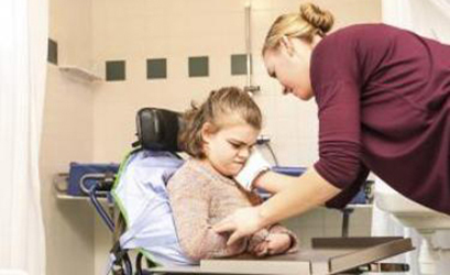 Young Caucasian girl with multiple disabilities wearing a pastel sweater is assisted by Caucasian nurse wearing