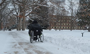 Viewed from the back, a person in a black winter coat rolls his wheelchair down a snowy and tree-lined pathway on what looks to be a college campus.