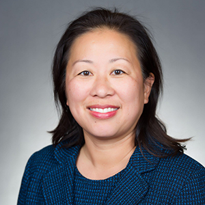 Asian american woman wearing a blue suit smiling at the camera.