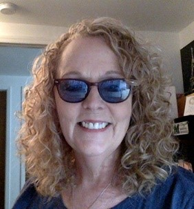 Photo of a Dena Gassner, Image of a smiling white woman with shoulder lengh curly hairs an wearing shaded glasses.