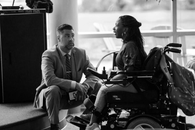 Man kneeling in front of a woman sitting in a wheelchair having a conversation.