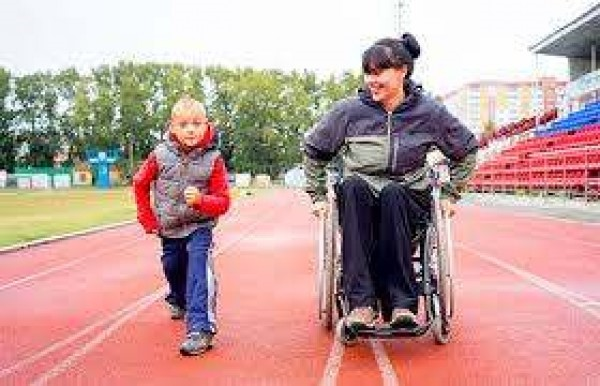 woman in a wheel chair racing a little boy on a track